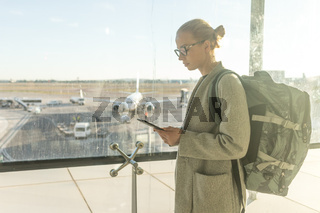 Casually dressed female traveler at airport looking at smart phone device in front of airport gate windows overlooking planes on airport runway