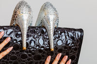 Black handbag and silver high heels shoes in female hands