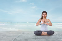 Young yogi woman is meditating on the beach in lotus position