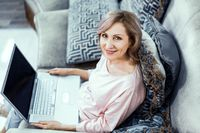 Smiling woman holds a laptop working from home