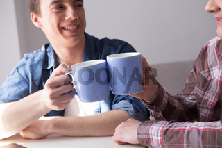 Two boys drinking coffee together.