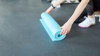 Junge Frau rollt Yogamatte aus im Fitnesscenter