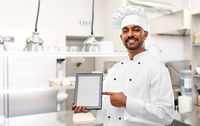 indian chef with tablet pc at restaurant kitchen
