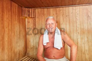 Senior sitzt lächelnd in der Sauna