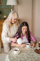 Senior female pouring tea from teapot into her daughter's cup