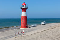 Lighthouse at dike with recreating people near Westkapelle, the Netherlands