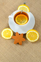 A cup of tea with slices of lemon and a two half lemons and one star cookies.