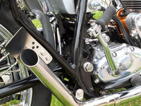 close up of the engine and chrome exhaust pipe of a vintages custom 1970s scrambler type motorcycle