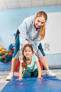 Sportlehrer hilft Mädchen beim Turnen