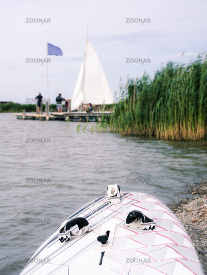 Lakeside Neusiedlersee with surf board and sailing boat