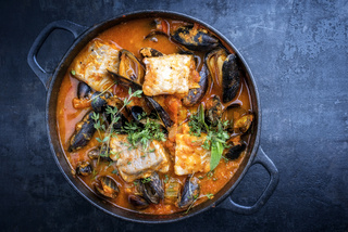 Traditional French Corsican fish stew with mussels as top view in a pot with copy space