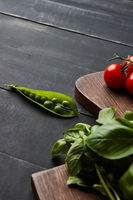 Fresh vegetables and spices of red and green colors on a wooden background