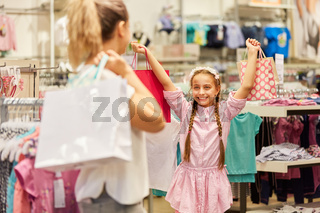 Mädchen zeigt Einkäufe ihrer Mutter