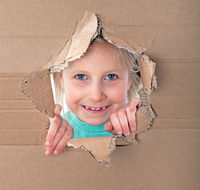 kid portrait in torn paper hole