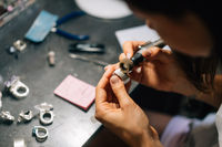 The girl works on a jewelry in the workshop