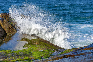 Waves crashing over rocks with water spray