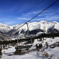 Chair-lift at ski resort and snowy winter mountains at nice sun day