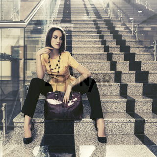 Young fashion business woman with handbag sitting on steps in office