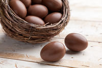 Delicious chocolate Easter holiday egg on rustic background