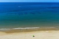 Einsamer Sonnenschirm auf einem leeren Sandstrand bei Praia da Luz