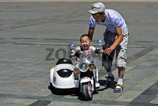 Kleinkind fährt mit Unterstützung seines Vaters ein elektrisch betriebenes Motorrad,Mongolei
