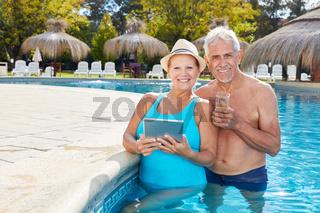 Senioren mit Tablet im Swimmingpool