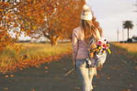 Woman walking along a country road in Autumn