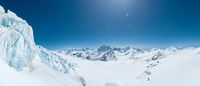 Winter snow covered mountain peaks in Caucasus. Great place for winter sports. Alpinirst climbs uphill with skis.