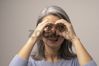 Mongolian Mature Woman Holds Hands As if Looking Through Binoculars.