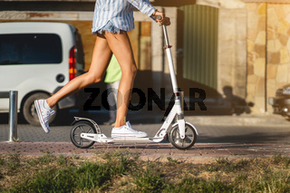 Beautiful girl riding a scooter down the street