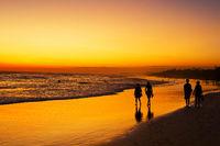 People walking ocean beach sunset