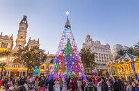 Christmas fair with colorful christmas tree and carousel on Modernisme Plaza of the City Hall of Valencia, Spain.
