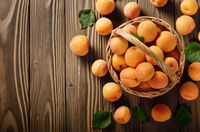 Top view of Wicker basket with ripe apricots on wooden table. Place for text