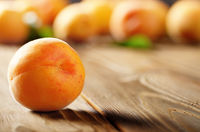 Ripe organic apricots on wooden table closeup view