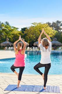 Frauen bei Yoga Meditation am Pool