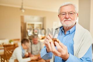 Alter Mann spielt mit einem Holzpuzzle