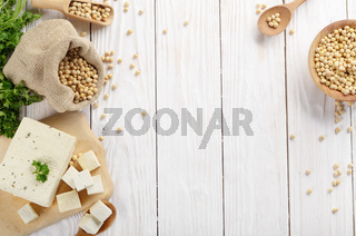 Soy Bean curd tofu on cutting board and in hemp sack on white wooden kitchen table. Space for text