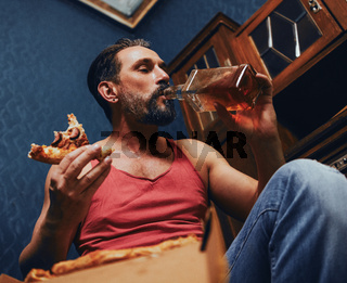 Brutal Bearded Man at Home Eating Pizza and Drinking Alcohol.
