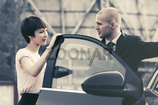 Happy young couple talking beside a car