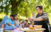 man using smartphone at picnic with friends