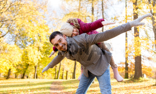 happy father and daughter playing at autumn park