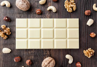 Delicious and sweet white chocolate on wooden background