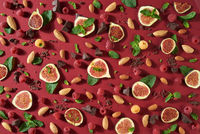 Creative sweet food composition from natural ingredients. Summer pattern with chocolate, berries, almond, figs, mint - ingredients for energy snack on a red background. Flat lay