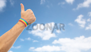 hand with gay pride rainbow wristband shows thumb