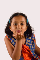 Little girl giving a flying kiss looking at camera. Pune, Maharashtra