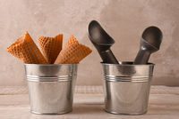 Closeup of ice cream cones in a small metal bucket next to a pail with two scoops
