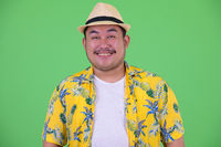 Face of happy young overweight Asian tourist man smiling