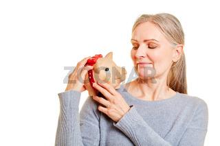 Ältere Frau trägt Sparschwein auf Schulter