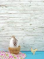 Ostern Hintergrund mit Osterei und Hahn auf blau vor Holz