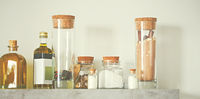 Selective focus of arranged jars with various spices and olive oil on kitchen shelf